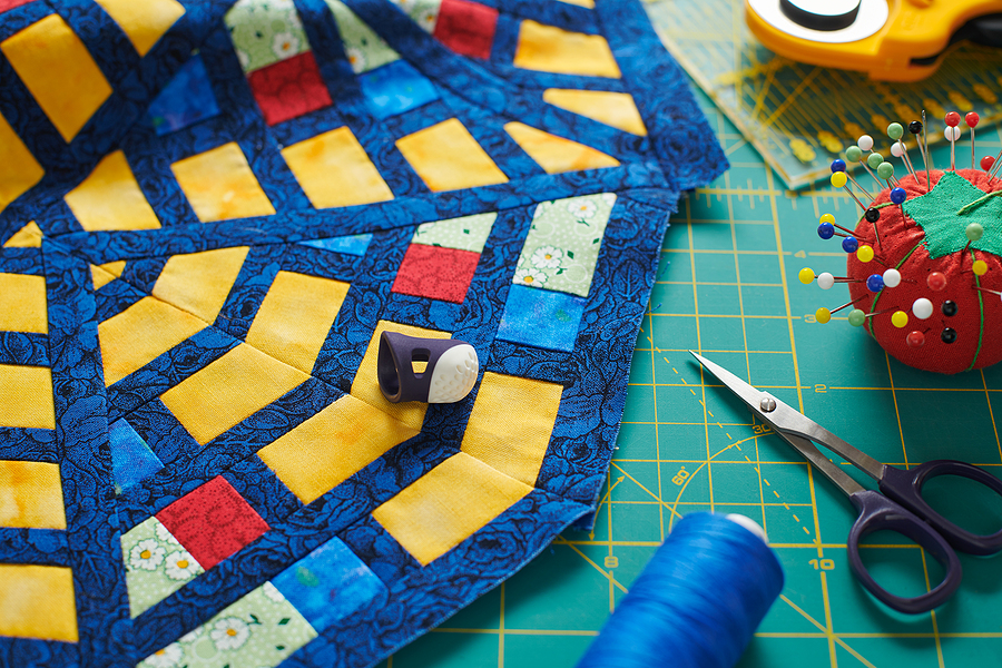 Fragment of a quilt, surrounded by tools for quilting